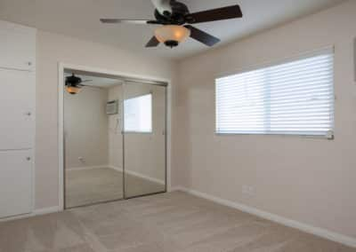 Bedroom with ceiling fan and mirrored closet