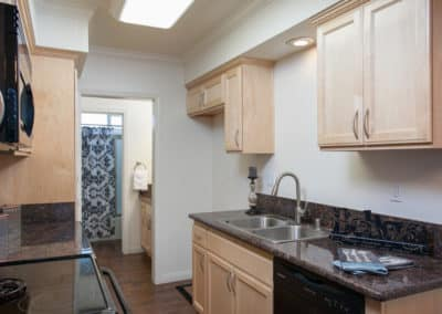 Galley kitchen with maple cabinets and granite counters